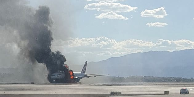 In this photo taken from the view of a plane window, smoke billows out from a plane that caught fire at McCarren International Airport, Tuesday, Sept. 8, 2015, in Las Vegas. An engine on the British Airways plane caught fire before takeoff, forcing passengers to escape on emergency slides. (Eric Hays via AP) MANDATORY CREDIT