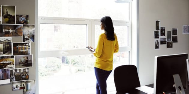 Female office worker looking out of a window.