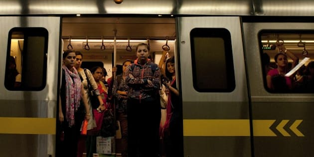Indian women are framed in the doorway as they travel in the carriage reserved for women on the metro in New Delhi on July 3, 2015.  AFP PHOTO/ Anna ZIEMINSKI        (Photo credit should read ANNA ZIEMINSKI/AFP/Getty Images)