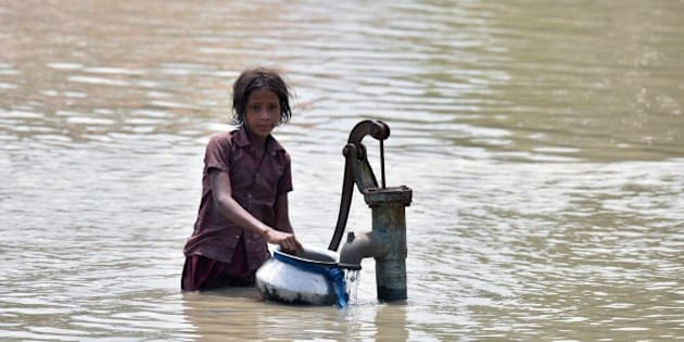 An Indian girl gets water from a partially submerged well in flood-affected Pavakati village, some 70 km from Guwahati in Assam state, on August 22, 2015. The Assam government has called on the army to help in rescue and relief efforts in flood-hit areas of the state. AFP PHOTO / Biju Boro        (Photo credit should read BIJU BORO/AFP/Getty Images)