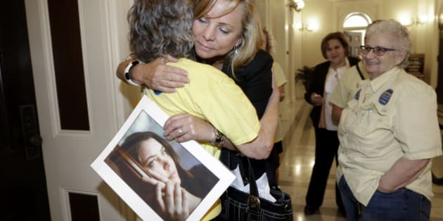 FILE - In this Sept. 9, 2015, file photo, Debbie Ziegler holds a photo of her daughter, Brittany Maynard, as she receives congratulations from Ellen Pontac, after a right-to die measure was approved by the Assembly in Sacramento, Calif. Maynard was a 29-year-old California woman with brain cancer who moved to Oregon to legally end her life. California lawmakers gave final approval Friday, Sept. 11, to a bill that would allow terminally ill patients to legally end their lives. The measure faces an uncertain future with Gov. Jerry Brown, a former Jesuit seminarian who has not said whether he will sign it. (AP Photo/Rich Pedroncelli, File)