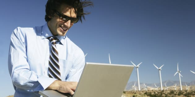 Young businessman using laptop near wind turbines.
