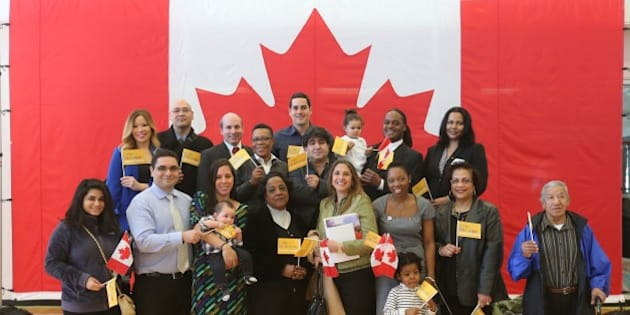 TORONTO, ON - APRIL 1:  Group shot of new Canadians who originate from countries that are competing in Pan Am Games pose for pictures at the Pan Am Games celebration, 100-day countdown with citizenship ceremony for 100 new Canadians at the CIBC Pan Am/Parapan Am Athletes' Village Cooper-Koo Family YMCA building in Toronto.        (Vince Talotta/Toronto Star via Getty Images)