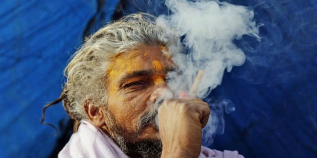 A Sadhu, or Hindu holy man, smokes marijuana to stay warm at Sangam, the confluence of rivers Ganges, Yamuna and mythical Saraswati in Allahabad, India, Sunday, Dec. 21, 2014. Intense cold wave continues unabated in north India with fog disrupting traffic movements at several places. (AP Photo/Rajesh Kumar Singh)