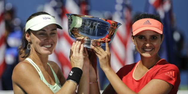 Martina Hingis, of Switzerland, left, and Sania Mirza, of India, hold up the championship trophy after defeating Casey Dellacqua, of Australia, and Yaroslava Shvedova, of Kazakhstan, in the women's doubles championship match of the U.S. Open tennis tournament, Sunday, Sept. 13, 2015, in New York. (AP Photo/David Goldman)