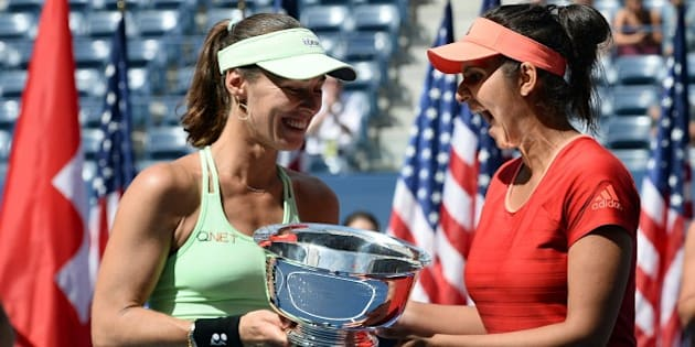 Sania Mirza (R) of India and her teammate Martina Hingis of Switzerland celebrate with their trophy after defeating Casey Dellacqua of Australia and Yaroslava Shvedova of Kazakhstan during their 2015 US Open Women's Double final match at the USTA Billie Jean King National Tennis Center in New York on September 13, 2015. AFP PHOTO/JEWEL SAMAD        (Photo credit should read JEWEL SAMAD/AFP/Getty Images)