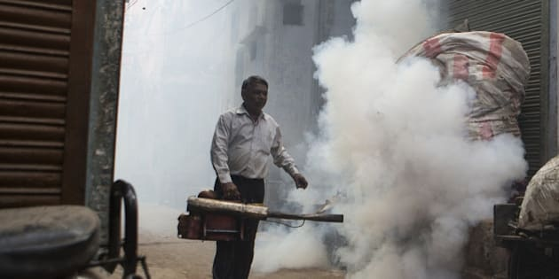 Indian labourer fumagates an alley to prevent dengue
