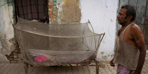 An Indian labourer walks past a women sleeping under a mosquito net in New Delhi early June 4, 2012.  Dengue fever caused by mosquito bites is a seasonal, sometimes fatal viral disease transmitted by the Aedes mosquito, which bites during the day. AFP PHOTO/ ANDREW CABALLERO-REYNOLDS        (Photo credit should read Andrew Caballero-Reynolds/AFP/GettyImages)