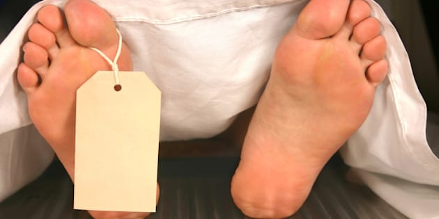 Two feet covered with a white sheet, with a toe tag.