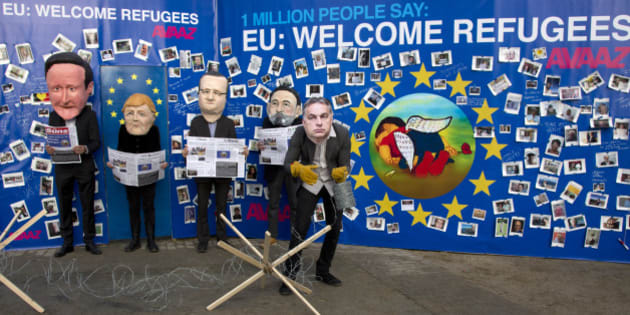 Actors dressed with face masks of EU leaders, from left, British Prime Minister David Cameron, German Chancellor Angela Merkel, French President Francois Hollande, Spanish Prime Minister Mariano Rajoy and Hungarian Prime Minister Viktor Orban pose in front of a painting of the late Aylan Kurdi on a refugee message board outside of EU headquarters in Brussels on Monday, Sept. 14, 2015. Aylan Kurdi, 3, was found dead on a Turkish beach after the small rubber boat he and his family were in capsized in a desperate voyage from Turkey to Greece. EU interior ministers meet on Monday to discuss the migration crisis. (AP Photo/Virginia Mayo)