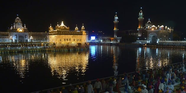 Indian Sikh devotees watch a fireworks display at the illuminated Sikh shrine Golden Temple in Amritsar on September 14, 2015. The event took place for the 411th anniversary of the installation of the Guru Granth Sahib, the holy book of the Sikh religion. AFP PHOTO/ NARINDER NANU        (Photo credit should read NARINDER NANU/AFP/Getty Images)