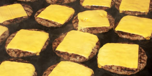 Beef hamburgers cooking on barbecue with melting cheese slice on top.