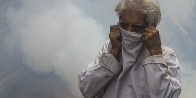 An Indian pedestrian protects his face as he is engulfed in a cloud of pesticide during a dengue prevention spraying in the Old Quarters in New Delhi on October 10, 2013. Nearly 1,400 dengue cases have been reported from the Indian capital and adjoining areas and at least five people have died of dengue in Delhi. AFP PHOTO/ Andrew Caballero-Reynolds        (Photo credit should read Andrew Caballero-Reynolds/AFP/Getty Images)