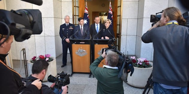 Australian Prime Minister Tony Abbott, Chief of the Australian Defence Force Mark Binskin (L), Defence Minister Kevin Andrews (2nd-L) listen to Foreign Minister Julie Bishop (R) addressing the media during a press conference at Parliament House in Canberra on September 9, 2015.  Australia will take an extra 12,000 refugees in response to the humanitarian crisis in the Middle East, Abbott said, confirming Canberra would join coalition air strikes against Islamic State group in Syria.       AFP PHOTO / MARK GRAHAM        (Photo credit should read MARK GRAHAM/AFP/Getty Images)