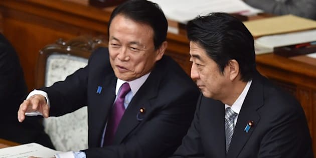 Japanese Finance Minister Taro Aso (L) speaks with Prime Minister Shinzo Abe (R) during a session at the National Diet in Tokyo on January 26, 2015. The National Diet convened a 150-day session with Finance Minister Taro Aso delivering a speech.   AFP PHOTO / KAZUHIRO NOGI        (Photo credit should read KAZUHIRO NOGI/AFP/Getty Images)
