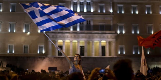 A supporter of the No vote waves a Greek flag in front of the parliament after the results of the referendum at Syntagma square in Athens, Sunday, July 5, 2015. Greeks overwhelmingly rejected creditors' demands for more austerity in return for rescue loans in a critical referendum Sunday, backing Prime Minister Alexis Tsipras, who insisted the vote would give him a stronger hand to reach a better deal. (AP Photo/Emilio Morenatti)