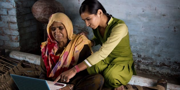 Happy villager girl using laptop with her happy mother.
