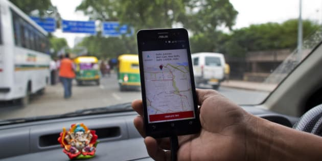 An Indian cab driver displays the city map on a smartphone provided by Uber as he drives in New Delhi, India, Friday, July 31, 2015. Ride-hailing service Uber has announced a $1 billion investment for the Indian market for the next nine months as it hopes to expand services and products, news reports said Friday. (AP Photo/Saurabh Das)