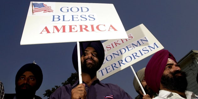 395648 07: Sikh men carry patriotic placards at a community service to remember victims of terrorist attacks, October 10, 2001 in Santa Ana, CA.Although Sikhs are not Muslims and come from India, they have been targeted in recent hate crimes because the men wear turbans and beards similar to terrorist suspect Osama bin Laden. (Photo by David McNew/Getty Images)
