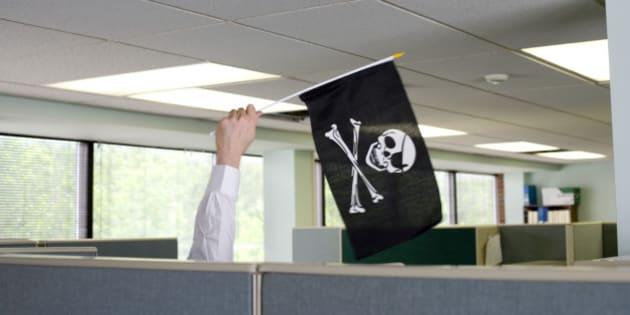 Businessman waving jolly roger flag cubicle wall