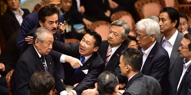 Opposition lawmakers surround chairman Yoshitada Konoike (L) as lawmaker Masahisa Sato (2nd L) gestures during the Upper House's ad hoc committee meeting on the controversial security bills, at the National Diet in Tokyo on September 17, 2015. Japan's ruling and opposition parties remained deadlocked in parliament early on September 17 over proposed security bills as thousands took to the streets in protests against legislation that could see troops fight overseas for the first time in 70 years. AFP PHOTO / Yoshikazu TSUNO        (Photo credit should read YOSHIKAZU TSUNO/AFP/Getty Images)