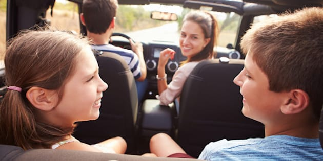 Parents Taking Children On Trip In Open Top Car