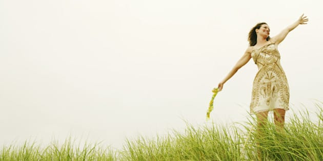Woman with outstretched arms in field