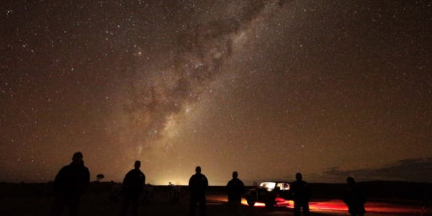 In this May 28, 2013 photo, tourists stand and gaze at the milky-way near Broken Hill, 1,160 kilometers (720 miles) from Sydney,  Australia, during a seven-day, 3,000-kilometer (1,900-mile) journey across the Outback. (AP Photo/Rob Griffith)