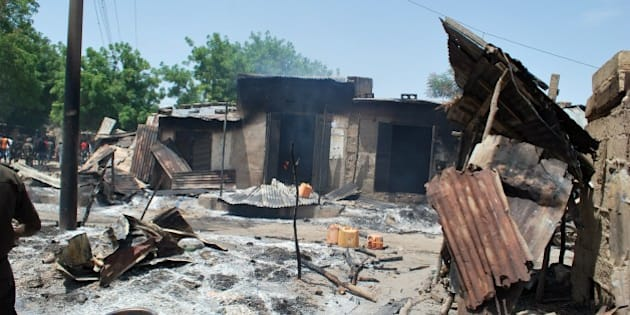 A photo taken on July 4, 2015 shows houses burnt by Boko Haram fighters at Zabarmari, a fishing and farming village near Maiduguri, northeast Nigeria.  Several female suicide bombers in northeast Nigeria blew themselves up amid panicked villagers fleeing a Boko Haram attack, killing scores, the army and witnesses said July 4. The latest carnage in series of attacks that have claimed more than 200 lives in just three days happened on Friday night in Zabarmari village, 10 kilometres (six miles) from the city of Maiduguri, the birthplace of the jihadist group. AFP PHOTO/STRINGER        (Photo credit should read STRINGER/AFP/Getty Images)