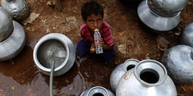 An Indian boy drinks water collected from a government water supply tap at an impoverished settlement on a hot summer day in Bhubaneswar, India, Saturday, May 30, 2015. Heat-related conditions, including dehydration and heat stroke, have killed more than 1,000 people in the southern Indian state of Andhra Pradesh and hundreds in Telangana since mid-April, according to state officials. (AP Photo/Biswaranjan Rout)