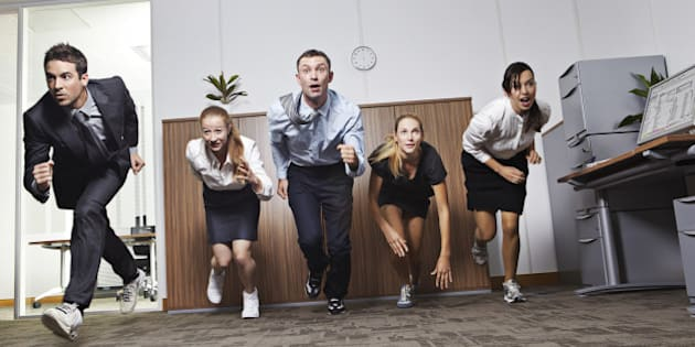 Businessmen and businesswomen racing in office