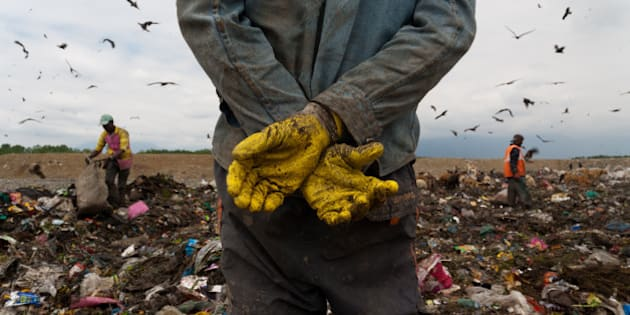 SRINAGAR, KASHMIR, INDIA - APRIL  29:  Indian laborers sort through the heaps of waste at the city's lone landfill site on April 29, 2015 in Srinagar, the summer capital of Indian administered Kashmir, India.  Kashmir has witnessed huge influx of poor migrant laborers from different parts of India over the past few decades. Living below poverty line and with little access to education or sanitary living conditions, whole families, including children, mostly from different Indian states collect scrap to make a living.  These Indian laborers sort through heaps of waste at a landfill site in Srinagar, where an average  400 metric tonnes of solid waste is dumped  on daily basis. Working at landfill sites can be hazardous and many of laborers do manual scavenging without basic precautionary equipment. Although the Indian economy has seen significant growth, there are still millions of people who survive on less than $1 (63 INR) a day. International Workers' Day, also known as Labour Day in some places is marked on May 1, 2015. (Photo by Yawar Nazir/Getty Images)
