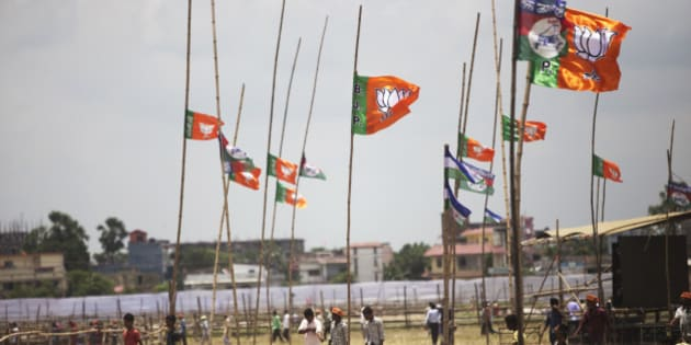 People walk past Bharatiya Janata Party (BJP) flags on bamboo poles in Muzaffarpur, Bihar, India, on Saturday, July 25, 2015. More than anywhere, Bihar reflects the challenge Prime Minister Narendra Modi faces in overhauling modern India. A vast, landlocked plain bordering the Himalayan nation of Nepal to the north and bisected by the Ganges, India's holiest river, the state is home to about one in 12 Indians. Photographer: Prashanth Vishwanathan/Bloomberg via Getty Images