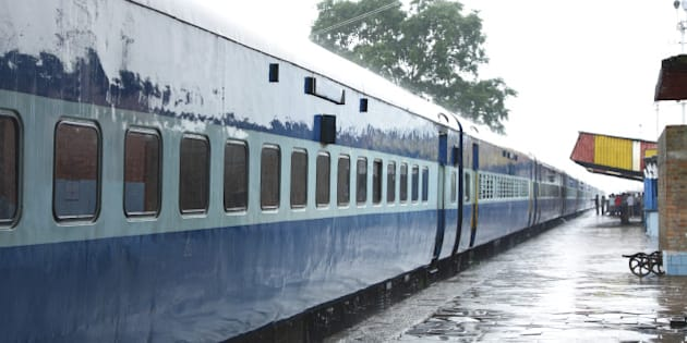 blue color coaches of indian train stainding in a station during rain