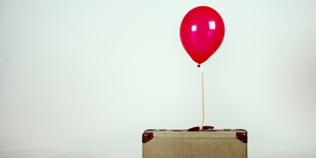 Red helium ballon tied to an old suitcase.