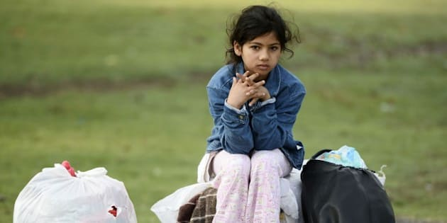 EDIRNE, TURKEY - SEPTEMBER 22: A refugee girl sitting on bags is seen at Edirne's Saraici square where the Syrian refugees camp while waiting for the borders to be opened on September 22, 2015 in Edirne, Turkey. Thousands of refugees continue to flock to Edirne, which borders Greece and Bulgaria, in an attempt to cross further into Europe. (Photo by Berk Ozkan/Anadolu Agency/Getty Images)