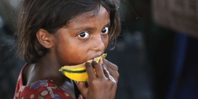 FILE - In this Friday, June 12, 2015 file photo, an Indian child laborer eats a piece of a muskmelon on the World Day against Child Labor on the outskirts of Jammu, India. Despite the country's rapid economic growth, child labor remains widespread in India, where an estimated 13 million children work, with laws meant to keep kids in school and out of the workplace routinely flouted. (AP Photo/Channi Anand, File)
