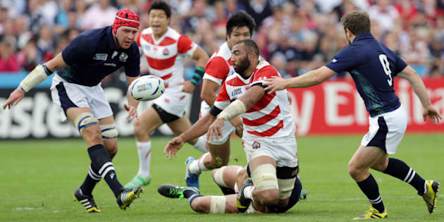 Japan's captain Michael Leitch, centre, throws the ball during the Rugby World Cup Pool B match between Scotland and Japan at Kingsholm, Gloucester, England, Wednesday, Sept. 23, 2015. (AP Photo/Clint Hughes)
