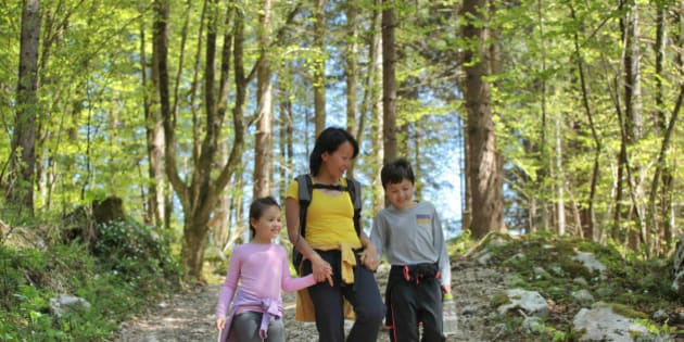 Mother holding her children's hands, walking and chatting happily in the forest.