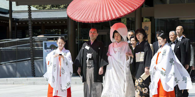 Japanese bride and groom with family and shrine maidens (Miko) at Shinto wedding ceremony, Meiji Jingu shrine, Tokyo, Japan