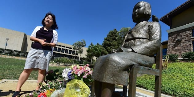 Activist Phyllis Kim of the Korean American Forum of California, stands beside the controversial Comfort Women Statue in Glendale, California on September 9, 2014, a day after reports that opponents of the statue have appealed the August decision by U.S District Judge Percy Anderson against removing the memorial dedicated to women who were coerced into sexual slavery during World War II by Japan, ruling the 1,100-pound memorial did not cause harm to the plaintiffs nor break any laws. The statue was installed at Glendale's Central Park in July 2013. AFP PHOTO / Frederic J. BROWN        (Photo credit should read FREDERIC J. BROWN/AFP/Getty Images)