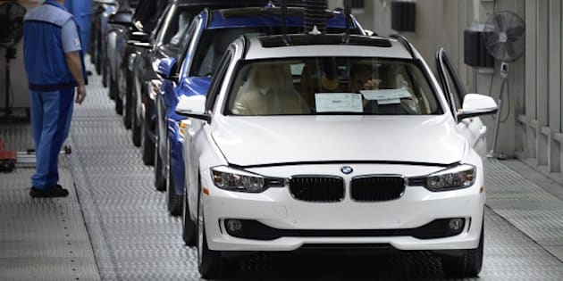 Employees of German car maker BMW work on an assembly line for BMW cars at the company's plant in Munich, southern Germany, on March 18, 2014. German top-of-the-range car maker BMW, who said on March 13, 2014 it achieved record sales and earnings and plans to pay an increased dividend to shareholders, will have its annual press conference on March 19, 2014.     AFP PHOTO / CHRISTOF STACHE        (Photo credit should read CHRISTOF STACHE/AFP/Getty Images)