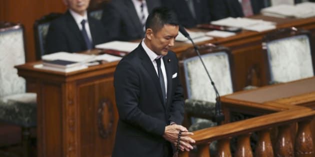 """Wearing a black tie, lawmaker Taro Yamamoto of Japan's opposition party """"Yamamoto Taro and his friends"""" prays with Buddhist prayer beads during a voting on a censure motion filed by Japan's major opposition Democratic Party of Japan against Prime Minister Shinzo Abe at the upper house plenary diet session in Tokyo, Friday, Sept. 18, 2015. The censure motion was filed by the opposition in their attempt to block contentious security bills that Abe's ruling Liberal Democratic Party is eager to get final approval by the upper house. Yamamoto raised on Thursday a sign reading: """"The day the LDP died"""" when the LDP pushed security bills through a legislative committee, catching the opposition by surprise and causing chaos in the chamber. (AP Photo/Koji Sasahara)"""