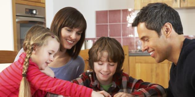 Family Playing Dominoes In Kitchen Sitting Around Having Fun