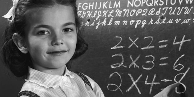 circa 1945:  An elementary schoolgirl points to multiplication tables on a blackboard.  (Photo by Lambert/Getty Images)