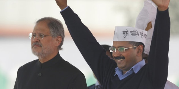 Aam Aadmi Party, or Common Man's Party, leader Arvind Kejriwal greets the crowd after taking oath as Chief Minister of Delhi, as Lieutenant Governor Najeeb Jung stands by his side in New Delhi, India, Saturday, Feb. 14, 2015. The AAP, headed by the former tax official who had remade himself into a champion for clean government, won 67 of the 70 seats in recent elections. Kejriwal and the party he created routed the country's best-funded and best-organized political machine and dealt an embarrassing blow to Prime Minister Narendra Modi. (AP Photo/Altaf Qadri)