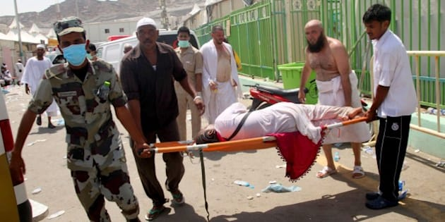 Hajj pilgrims and Saudi emergency personnel carry a woman on a stretcher at the site where at least 450 were killed and hundreds wounded in a stampede in Mina, near the holy city of Mecca, at the annual hajj in Saudi Arabia on September 24, 2015. The stampede, the second deadly accident to strike the pilgrims this year, broke out during the symbolic stoning of the devil ritual, the Saudi civil defence service said. AFP PHOTO / STR        (Photo credit should read STR/AFP/Getty Images)
