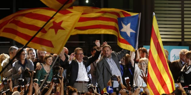 """Estelada"" or pro independence flags are waved in front of the President of Democratic Convergence of Catalonia Artur Mas, left and Oriol Junqueras, president of the Esquerra Republicana de Catalunya party in front of supporters in Barcelona, Spain, Sunday Sept. 27, 2015. Voters in Catalonia participated in an election Sunday that could propel the northeastern region toward independence from the rest of Spain or quell secessionism for years. An exit poll predicts that pro-independence parties in Spain's Catalonia region are likely to win a majority of seats in the regional parliament, but it's unclear whether they would be able to come together to push together on a plan to secede from Spain. (AP Photo/Manu Fernandez)"
