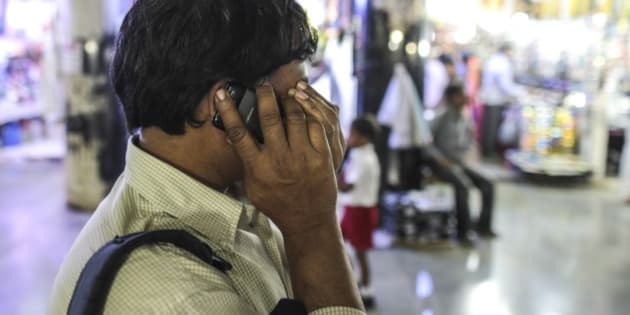 A man reacts while talking on a Karbonn Mobiles India Pvt. phone outside Chhatrapati Shivaji Terminus railway station during the morning rush hour in Mumbai, India, on Thursday, Feb. 26, 2015. The government auction of telecom wireless spectrum starting March 4 is expected to raise as much as $15.6 billion from service providers including those controlled by billionaires Kumar Mangalam Birla, Sunil Mittal and Anil Ambani, according to ICRA Ltd. Photographer: Dhiraj Singh/Bloomberg via Getty Images