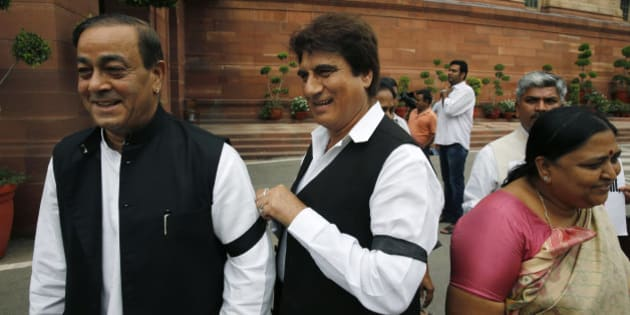 A Congress party lawmaker ties a black band on his colleague's hand during a protest in the Parliament premises in New Delhi, India, Friday, Aug. 7, 2015. The opposition continued their protests Thursday demanding that two leaders of the ruling Bharatiya Janata Party resign for allegedly helping a former Indian cricket official facing investigation for financial irregularities. (AP Photo/Manish Swarup)